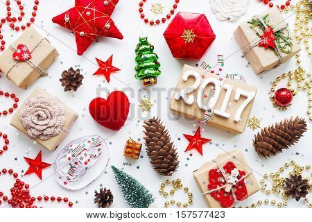 Christmas and New Year 2017 background with decorations. Gifts in craft paper pine cones red hearts and confetti. Flay lay top view.
