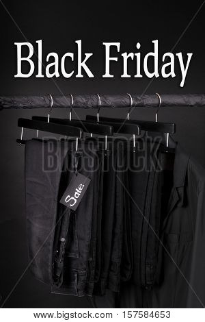 Black Friday Sign.  A Lot Of  Pants Jeans And Jacket Hanging On Clothes Rack.  Background.