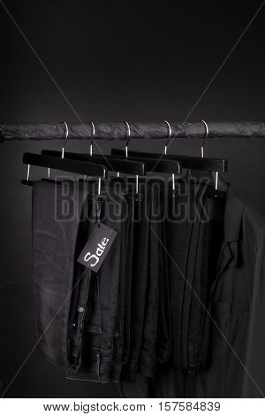 Sale Sign.  A Lot Of Black Pants Jeans And Jacket Hanging On Clothes Rack.  Background.  Friday. Cop