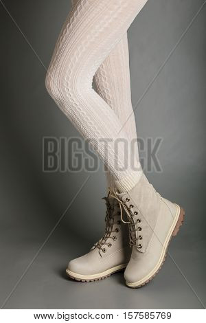 Female legs in white tights and bright winter boots.