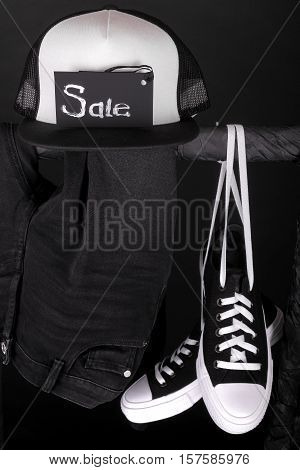 Sale Sign. Black And White Sneakers, Cap  Pant, Jeans Hanging On Clothes Rack   Background.   Friday
