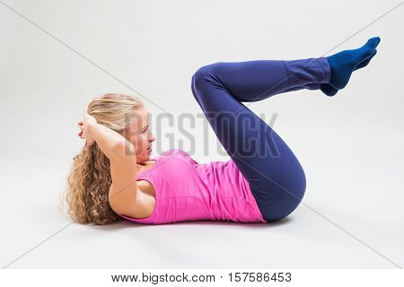 Studio shot image of young woman who is doing crunches.