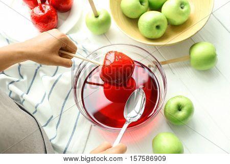 Female hands making caramel apples