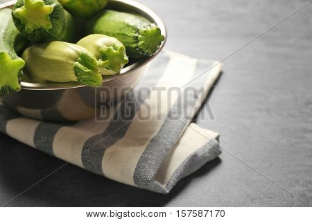 Composition with fresh zucchini in metal bowl and napkin on gray background