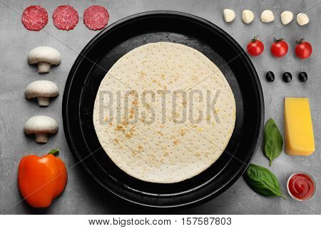 Pizza basis in baking tray and raw vegetables on grey background, top view