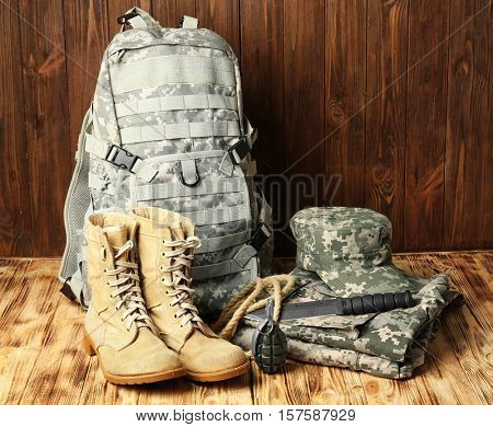 Set of military outfit on wooden background