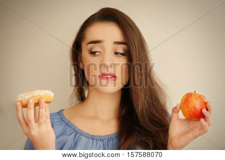 Beautiful young woman making choice between apple and donut on light background