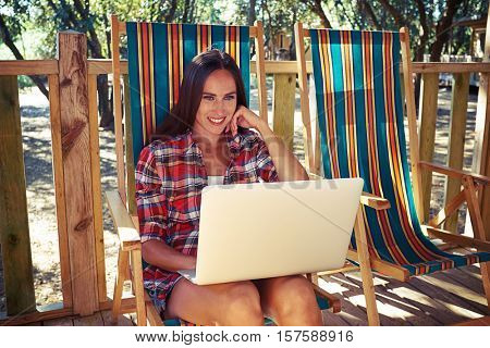 Wide shot of the pretty tanned woman who is sitting with a laptop on a summer beach chair. Checking her e-mail during the vacation. Summer holidays. To be in touch via modern technology