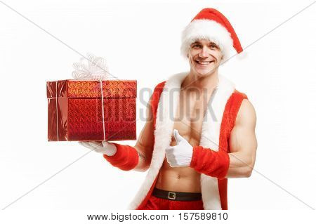 Fitness Santa pointing like a red box. Muscular Santa Claus holding a Christmas present in red box. Fitness Santa Happy New Year. Bodybuilder Santa with a red box on white background. Sexy Santa Claus