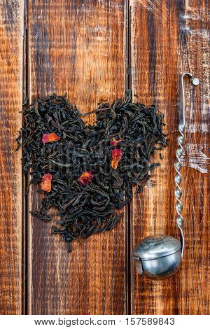 Vintage Strainer Near Dry Leaves Of Black Tea Make In Heart On Wooden Background.  Concept.  . Top V