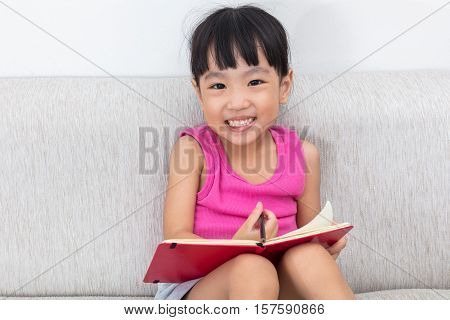 Happy Asian Chinese Little Girl Sitting On Sofa Writting Book