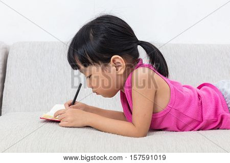 Asian Chinese Little Girl Laying On The Sofa Writting Book