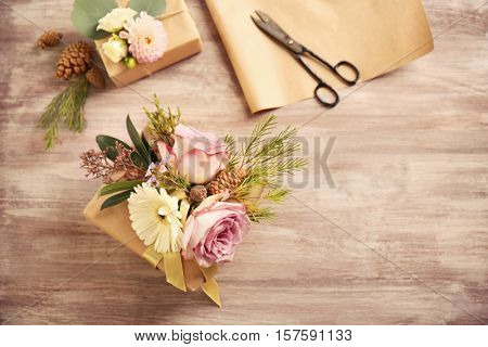 Handcrafted gift box with flowers and scissors on wooden table
