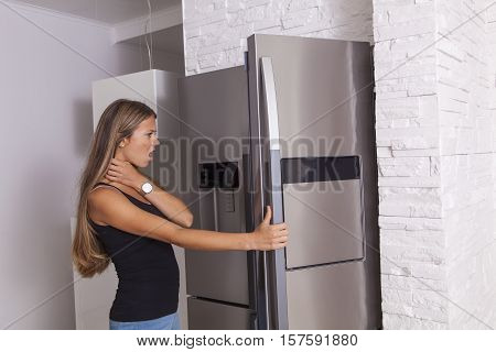 Blonde girl opening a fridge and looking into it with scared disgusted face one hand on her neck and one on the fridge handle