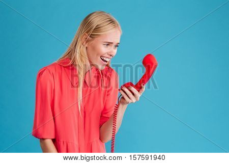 Portrait of a smiling attractive woman in red dress looking at red phone tube isolated on a blue background