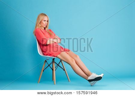 Full length portrait of a sad grumpy girl in red dress sitting on chair and looking away isolated on the blue background