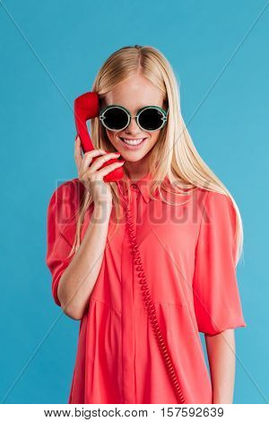 Cheerful stylish woman talking on the phone tube and looking at camera isolated on a blue background