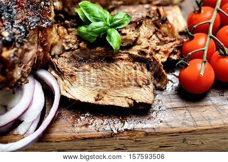 grilled  steak, cherry tomatoes and basil on a cutting board