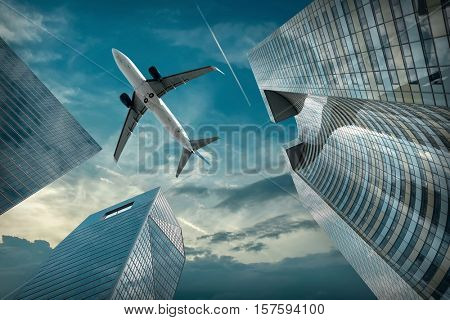 Airlane flying over modern glass and steel office buildings near La Defence district in Paris, France.