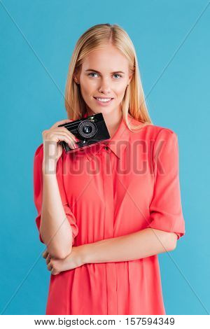 Portrait of a young woman photographer in dress standing with retro camera over blue background
