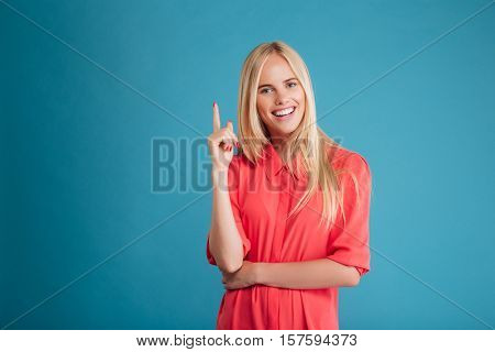 Smiling young happy woman poiting finger up at copyspace isolated on a blue background