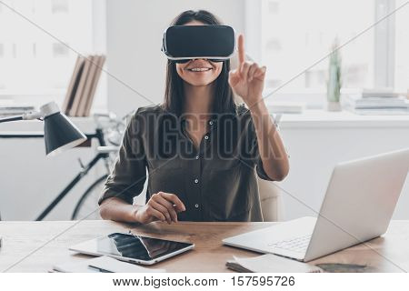 It seems so real. Confident young woman in virtual reality headset pointing in the air while sitting at her working place in office