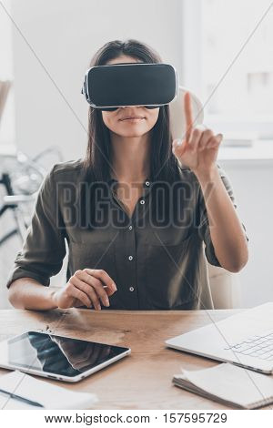 It seems you can touch it. Confident young woman in virtual reality headset pointing in the air while sitting at her working place in office