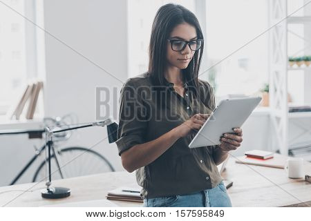 Working in office. Confident young woman in smart casual wear working on digital tablet while standing near her working place