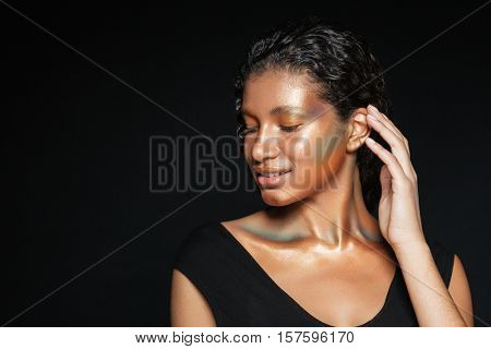 Happy african woman in t-shirt in studio. eyes closed. and near the ear. isolated black background