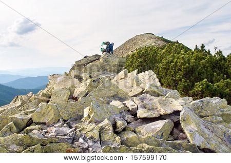 Traveler climbing to the mountain top through boulders