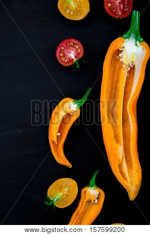 Mixed Of Half Red And Yellow Pepper With A Green Branch Near Cherry Tomato On  Black Background. Top