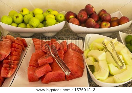 Cut fresh watermelon and melon. Assortment of fresh fruit on a table, red and green apples, tangerines. (selective focus)