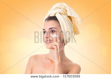 girl takes care her skin with towel on head smeared with cream isolated on white background. Health care concept. Body care concept. Young woman with healthy skin.