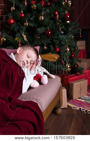 Boy sleeping under a blanket on the sofa near the Christmas tree with gifts