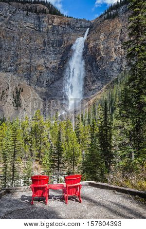 Autumn day in Yoho National Park in the Rocky Mountains of Canada. Two wooden red deckchairs for tourists opposite the famous waterfall