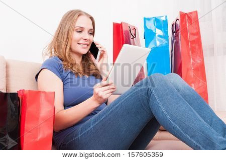 Lady Talking At Phone And Shopping Online Holding Tablet