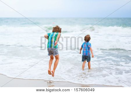 Two happy little kids boys running on the beach of ocean. Funny cute children, sibling and best friends making vacations and enjoying summer on stormy windy day.