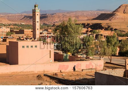 View from a roof on a small city Ait ben Haddou in Morocco. Tower of a mosque surrounded by trees. Atlas Mountains on the horizon. Blue morning sky.