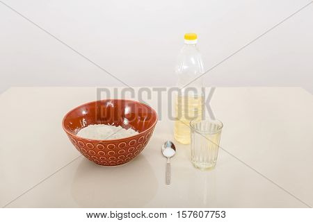 White wheat flour in a bowl with a metal spoon salt, a glass cold water and a bottle sunflower oil