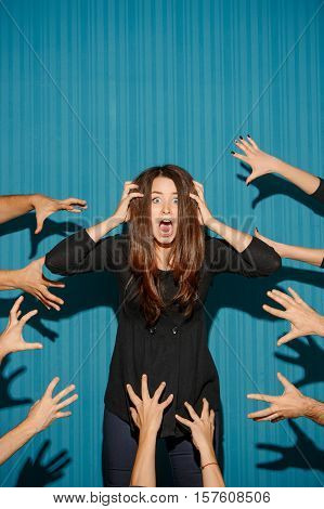 Portrait of young woman with shocked facial expression over blue studio background and mane people hands