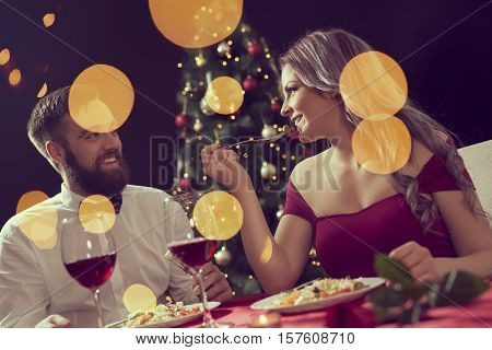Beautiful couple sitting at a table having a romantic Christmas dinner and enjoying their time together. Focus on the girl