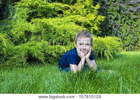 cute little boy sitting on the grass in landscape park