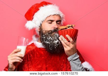 handsome bearded man with stylish mustache and long snowy beard on serious face holding and sniffing chocolate chip cookies in red santa suit on studio background