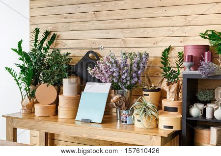 Small business. Modern flower shop interior. Floral design studio, sale of decorations and arrangements. Flowers delivery service and sale of home plants in pots, wooden showcase.