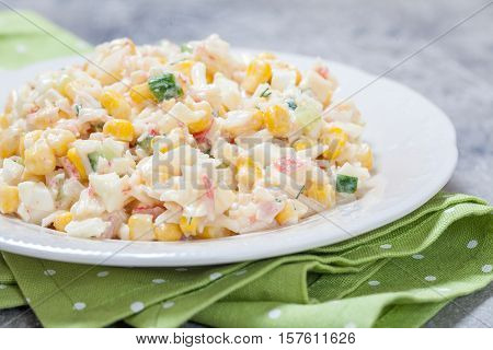 Delicious salad with crab sticks, corn, cucumber, and eggs