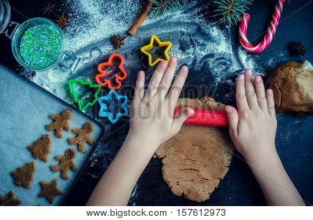 Hands of little girl sheeting dough with rolling pin. Christmas baking preparation. Child's hands with a rolling pin baking Christmas gingerbread cookies. Christmas cookies concept. Top view.