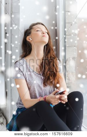 people, winter, christmas, technology and teens concept - sad pretty teenage girl sitting on windowsill with smartphone and earphones listening to music over snow