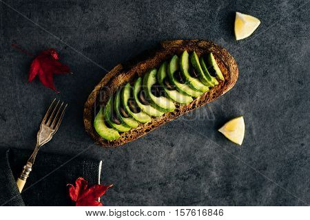Horizontal View of Wholemeal Slice of Bread with Avocado and Black Olives on Slate