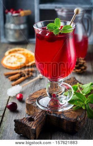 Fresh cranberry juice with cinnamon and anise in glass jars on the old wooden background. Selective focus.