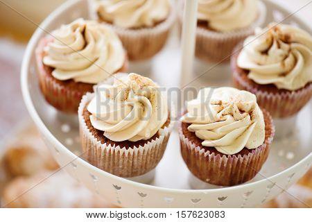 Close up, cupcakes with vanilla cream in white cakestand. Studio shot.